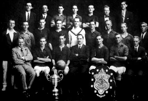 "Stella Football Club - 1922 (Dewar Shield and Charity Cup Winners) Back Row: E.R. Brokensha; R. Moore; C. Stephenson; S. Martyn; L. MacRae; C. Tucker; R. Cutbush. Standing: F. Scoones; A.V. Harrison; A.W. Scoones; H. Davis; R. Scoones; H. Millyard; Herbert Clark; C. Roper; S. Veckranges. Seated: William ""W.T."" Clark; A Hutchinson; Edgar Clark (Captain); W.H. Sperryn (President); V. Clarkson (Vice Captain); Alfred Clark; A. Williams"