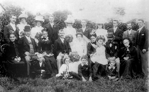 "Clark - McConnell Wedding Group (March 1900) Standing: ?; Mary Jane ""May"" Clark; Edith Hannah Clark; George Henry Clark; Eva McConnell; Christopher Clark; Alice McConnell; Arthur McConnell; Jack Clark; Andrew McConnell. Seated: Great G.M. McConnell; Peter McConnell; Mrs. P. McConnell (nee Lee); Thomas William Clark; Marion Clark (nee McConnell); Hannah Clark (with Muriel Alice Clark); George Clark (sr.); Great G.M. Mary Marcus. Foreground: Peter Joseph Clark; Emily Clark; Francis ""Frank"" Clark; Leonard James Clark"