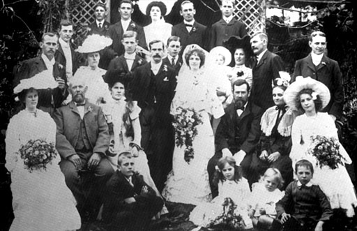 "Burden - Clark Wedding Group (September 29, 1903) Top: ?; Alf Eales; May Eales; Christopher Clark; Peter Clark Standing: ?; ?; ?; ?; William Burden; ?; Edith Clark (""Bonnie""); Edith Marion Clark; Marion Clark (nee McConnell); Tom Clark; George Clark Seated: ?; ?; Thursa Burden; George Clark; Hannah Clark; Emily Clark; Foreground:?;	Muriel	Clark; Arthur Clark; Leonard Clark"
